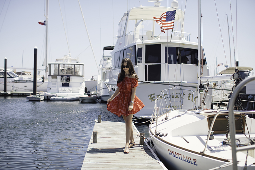 Liv walking on a dock in Newport Rhode Island just steps away from the Newport Marriott wearing an off the shoulder dress by Faithful the Brand.