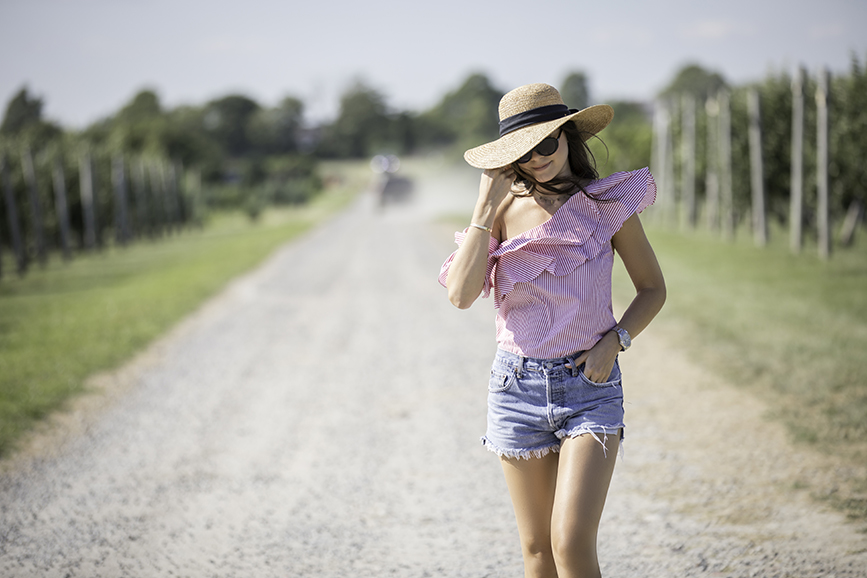Liv walking at the Sweetberry Farm in Newport Rhode Island about to pick raspberries and strawberries wearing vintage Levi shorts by Re Done, a L'academie top, and a Scala hat