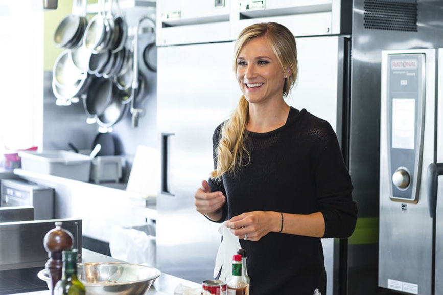 Brianne Theisen-Eaton smiling in a kitchen for the Liv For Luxury Cooking Contributor Series