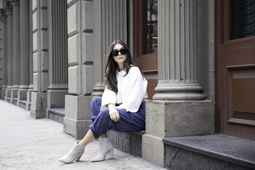 Liv Micheli sitting in SoHo wearing OFF WHITE c/o Virgil Abloh x Warby Parker Medium sunglasses, Urban Outfitters Roll neck Cropped Sweater, Silence + NoiseRelaxed-Fit trousers and Kenneth Cole boots.