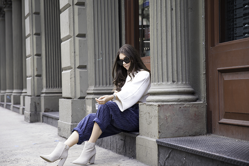 Liv Micheli sitting in SoHo wearing OFF WHITE c/o Virgil Abloh x Warby Parker Medium sunglasses, Urban Outfitters Roll neck Cropped Sweater, Silence + Noise Relaxed-Fit trousers and Kenneth Cole boots.