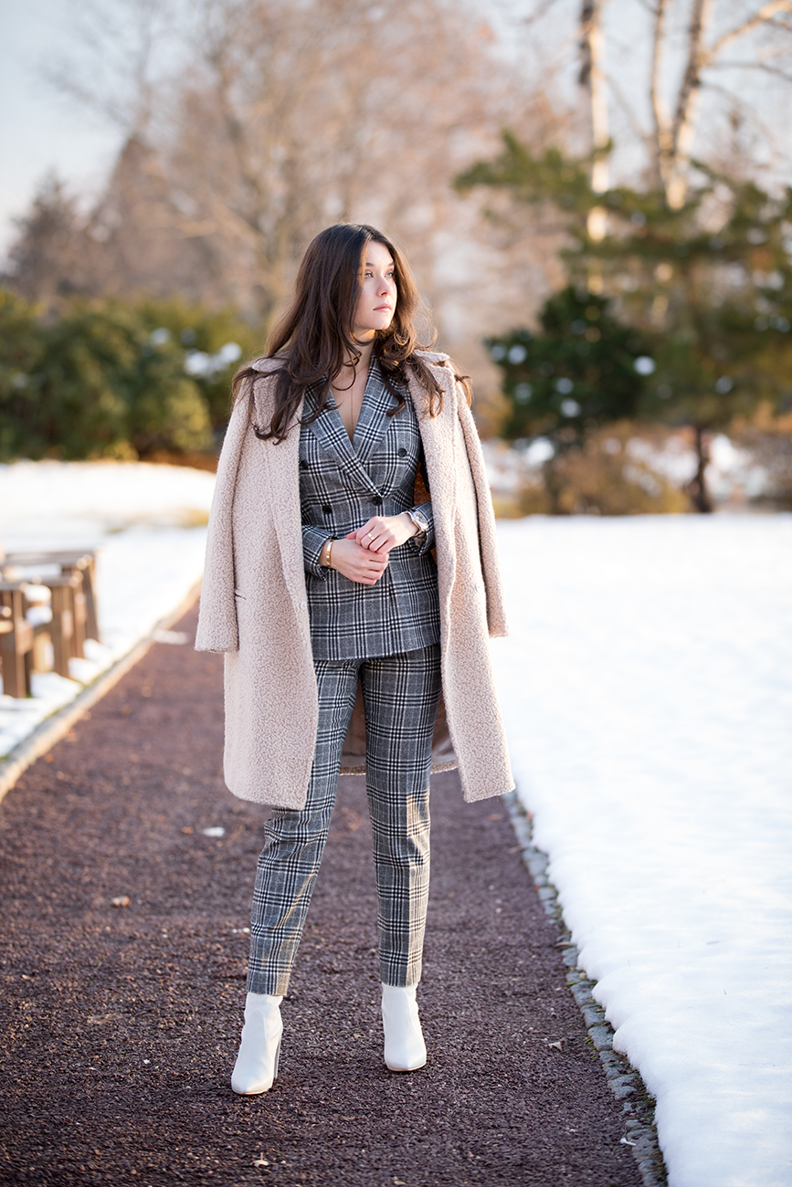 Blogger and Influencer, Liv Micheli, is wearing the SUISTUDIO Cameron Grey Checked Suit, the Light Brown Overcoat and Stuart Weitzman Clinger Boots in white leather at Westchester Country Club
